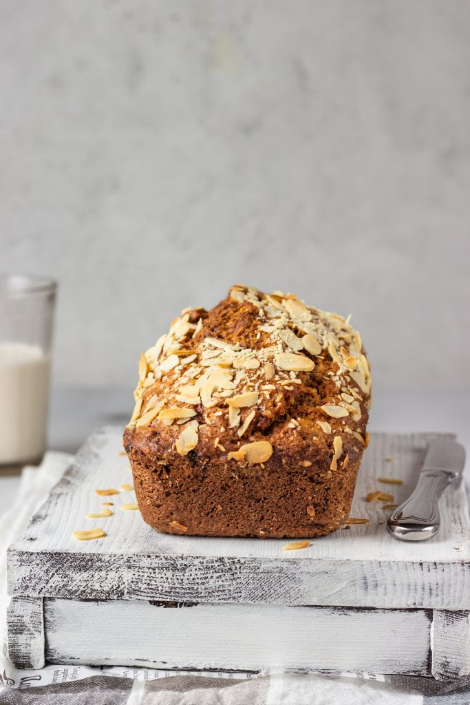 Butter-free and sugar-free banana bread with almond on a light grey wooden tray. Ideas and recipes for healthy diet breakfast. Selective focus.